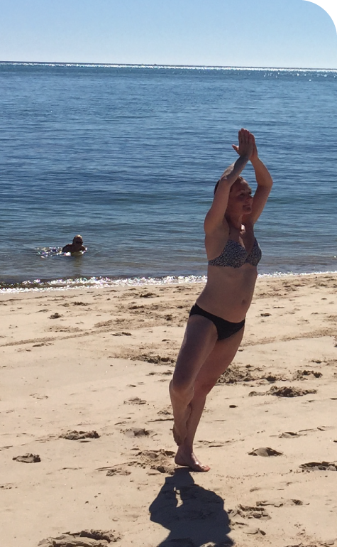Woman doing tree pose near the sea
